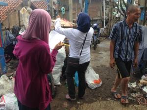 Teman saya dibantu seorang ibu warga setempat mendata sampah
